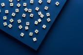 felső nézet betűk kockák szétszórva kék háttér