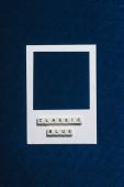 Draufsicht klassisch blauer Schriftzug auf Würfeln und weißem Fotorahmen mit strukturiertem blauem Hintergrund