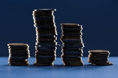 Stacks of metal coins in shadow on blue background stock vector
