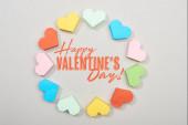 Horní pohled na rámeček barevných papírových srdcí na šedém pozadí se šťastným Valentýnským nápisem