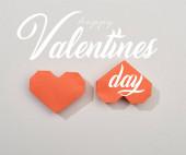 Horní pohled na dvě červená papírová srdíčka na šedém pozadí se šťastným Valentýna nápisy