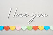 Top view of decorative papers in heart shape on grey background with i love you lettering