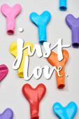 Horní pohled na barevné balónky ve tvaru srdce na šedém pozadí s pouhou láskou ilustrace