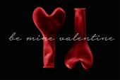 Horní pohled na dva červené balónky ve tvaru srdce izolované na černé s důlním valentýnským písmem