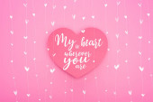 top view of paper heart with my heart is wherever you are lettering isolated on pink