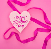 Fotografie top view of paper heart with happy valentines day illustration and ribbon isolated on pink