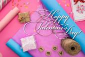vrchní pohled na valentinky dekorace, balicí papír, motouzy, dárkové krabice, přání a láska nápisy na dřevěné kostky na růžovém pozadí s šťastným Valentýna ilustrace