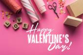 vrchní pohled na valentinky dekorace, nůžky, dárkové krabice, balicí papír a láska nápisy na dřevěné kostky na růžovém pozadí s šťastným Valentýna ilustrace
