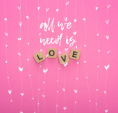 Fotografie top view of love lettering on wooden cubes on pink background with all you need is love illustration