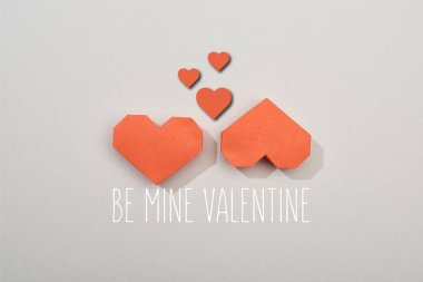 Top view of two red paper hearts on grey background with be mine valentine lettering stock vector