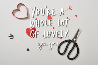 Top view of heart shaped papers with arrows and scissors on grey background with you are a whole lot of lovely lettering stock vector