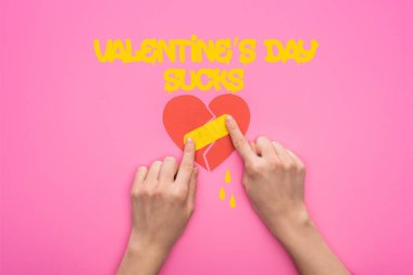 cropped view of woman putting patch on broken paper heart isolated on pink with valentines day sucks lettering