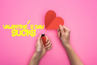 cropped view of woman lighting up empty red paper heart with lighter isolated on pink with valentines day sucks illustration