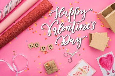 Top view of valentines confetti, scissors, wrapping paper, gift boxes, greeting cards and love lettering on wooden cubes on pink background with happy valentines day illustration stock vector
