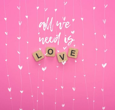 Top view of love lettering on wooden cubes on pink background with all you need is love illustration stock vector