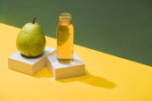 fresh juice in bottle near pear and white cubes on green and yellow background