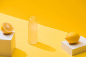 fresh juice in bottle near lemons and white cubes on yellow background