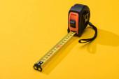 Průmyslová měřicí páska se stínem na žlutém pozadí