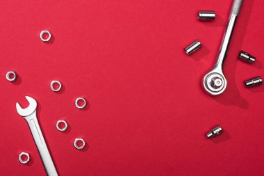 Top view of wrenches with nuts and nozzles on red background