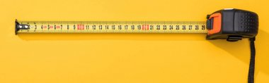 Top view of industrial measuring tape on yellow background, panoramic shot