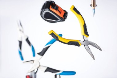 Selective focus of pliers, soldering iron and measuring tape levitating in air isolated on white
