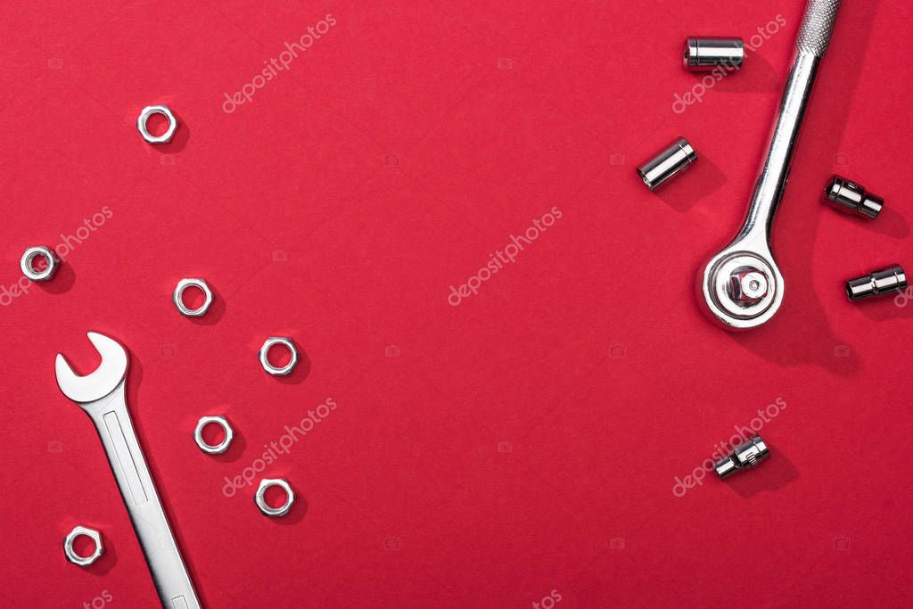 Top view of wrenches with nuts and nozzles on red background stock vector