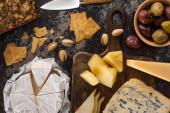 vrchní pohled na sýrový talíř s pistáciemi, plátky hrušky, olivami a sušenkami na ošlehaném povrchu