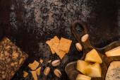 vrchní pohled na sýrový talíř s pistáciemi a sušenkami na ošlehaném povrchu