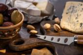 selektivní zaměření dorblu a brie sýra s olivami a pistáciemi u nože