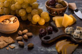 cheese platter with olives, fruits, crackers and pistachios near knife