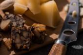 selektiver Fokus von Nusskäsestücken und Grana Padano neben Messer auf Schneidebrett