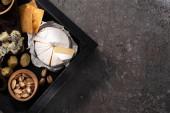 Ansicht des Tabletts mit Camemberstücken, Dorblu, getrockneten Oliven, Crackern, Pistazien auf grauem Hintergrund