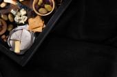 Ansicht des Tabletts mit Camemberstücken, Dorblu, getrockneten Oliven, Crackern und Pistazien isoliert auf schwarz