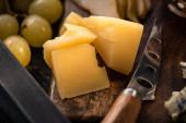 Selektivní zaměření kousků sýra a nože na řeznou desku vedle hroznů na podnose