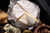 selektiver Fokus von Camembert-Stücken mit Crackern, Schüssel mit Pistazien, Dorblu und Oliven auf Tablett