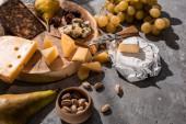 Různé druhy sýrů s ovocem, olivami, pistáciemi, na dřevěné desce na šedém pozadí
