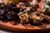 selektiver Schwerpunkt von Nusskäsestücken mit Oliven auf rundem Holzbrett