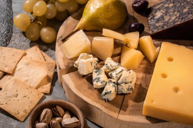 Selective focus of different kinds of cheese with pear and olives on wooden board next to grapes, nuts and crackers stock vector