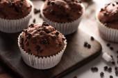 zblízka pohled na čerstvé čokoládové muffiny s marshmallow na dřevěné řezací desce