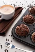 fresh chocolate muffins in muffin tin near brown napkin with coffee