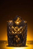 facettiertes Glas mit Eiswürfel und spritzendem Wodka im Dunkeln mit warmem Gegenlicht