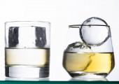 transparentní sklenice se zlatou tekutinou a ledem izolované na bílém