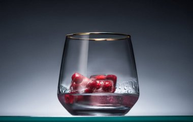 transparent glass with frozen redcurrant in ice cubes and vodka in dark with back light
