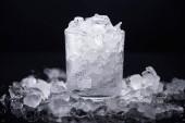 transparentes Glas gefüllt mit Scherbeneis isoliert auf schwarz