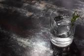 transparentes Glas mit Rosmarin, Eiswürfel und Wodka auf verwitterter Oberfläche