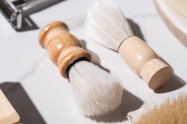 Selective focus of shaving brushes on white background, zero waste concept stock vector