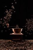 mlýnek na kávu a čerstvá pražená kávová zrna ve vzduchu izolované na černé