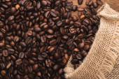 Photo top view of fresh roasted coffee beans scattered from sack on wooden surface