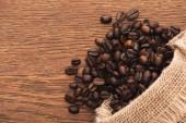 vrchní pohled na čerstvě pražená kávová zrna roztroušená z pytle na dřevěném povrchu