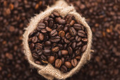 selective focus of fresh roasted coffee beans in sack